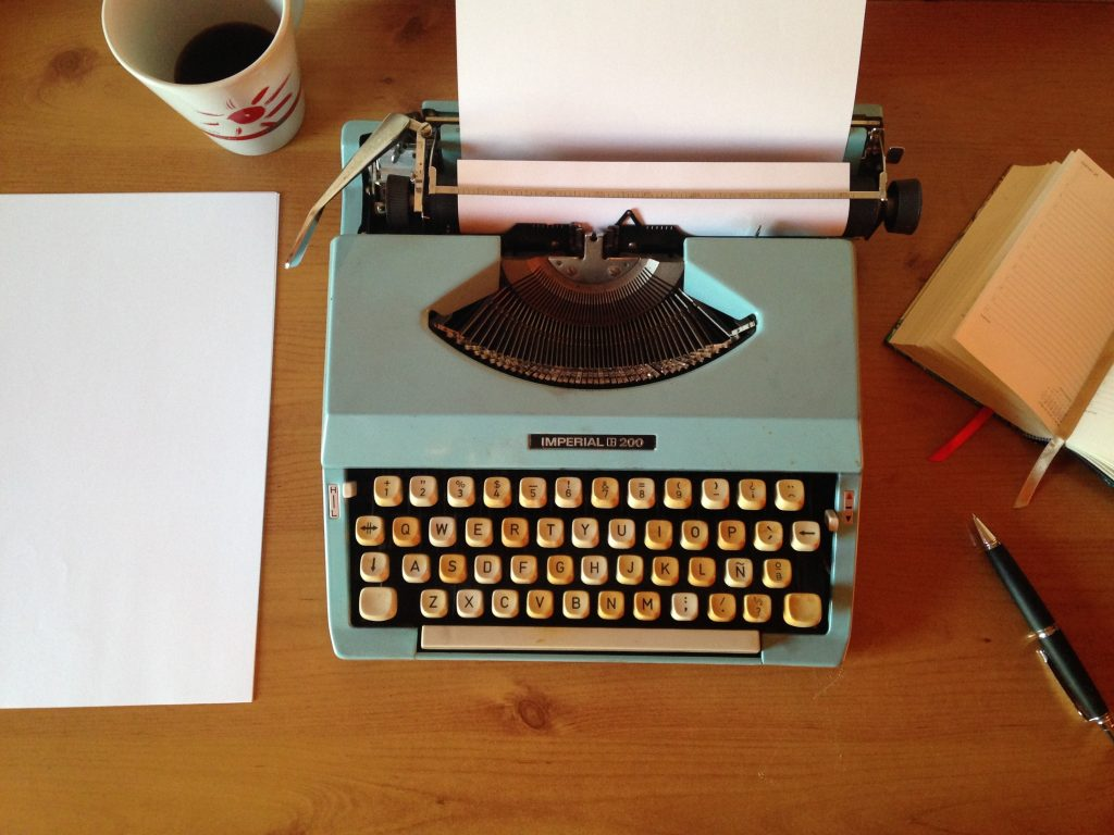 Typewriter, notebook, and cup of coffee