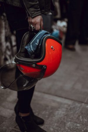 Photo of a woman holding a motorcycle helmet