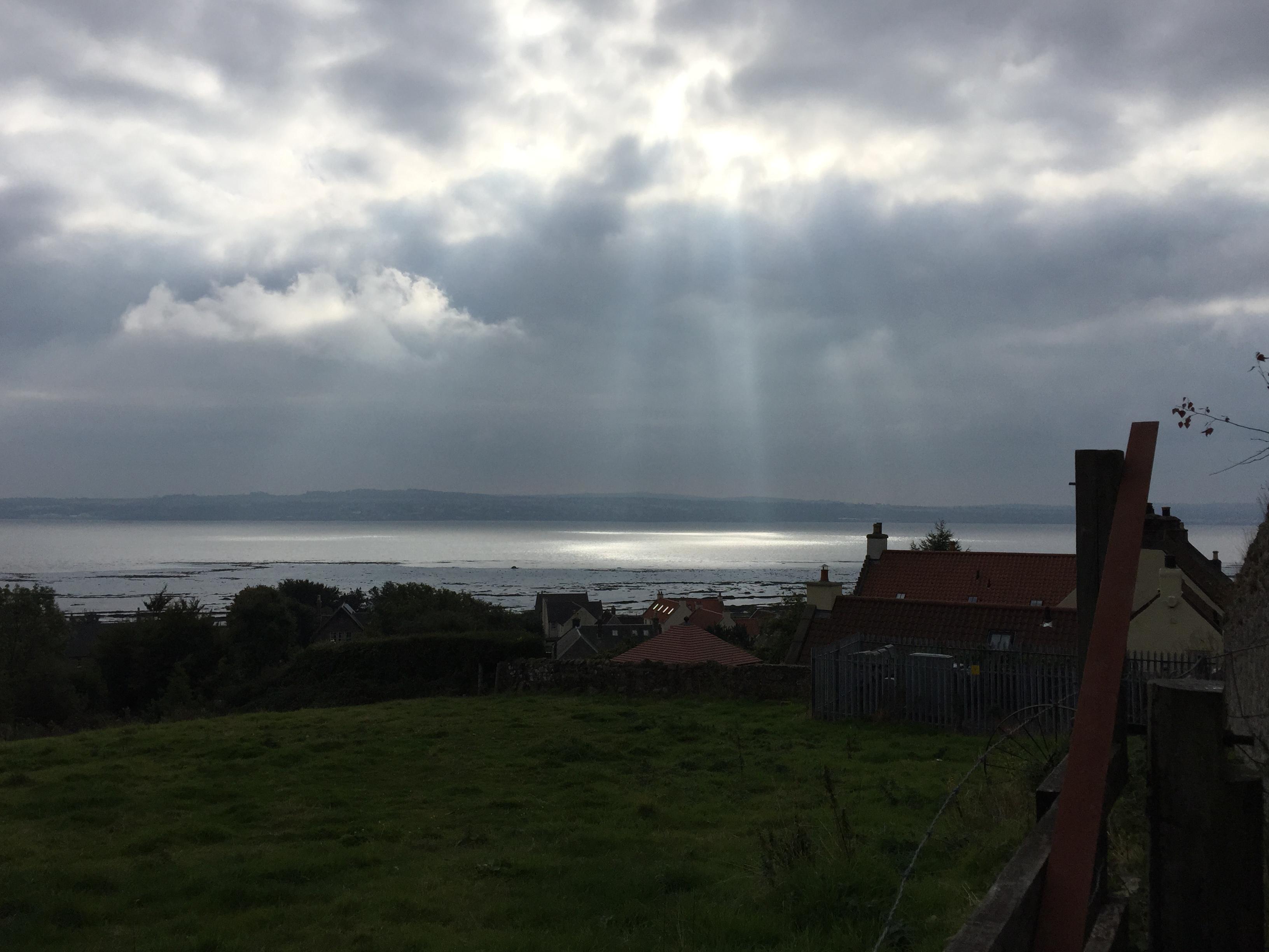 Sunlight shining on the water through clouds near Culross, Scotland.