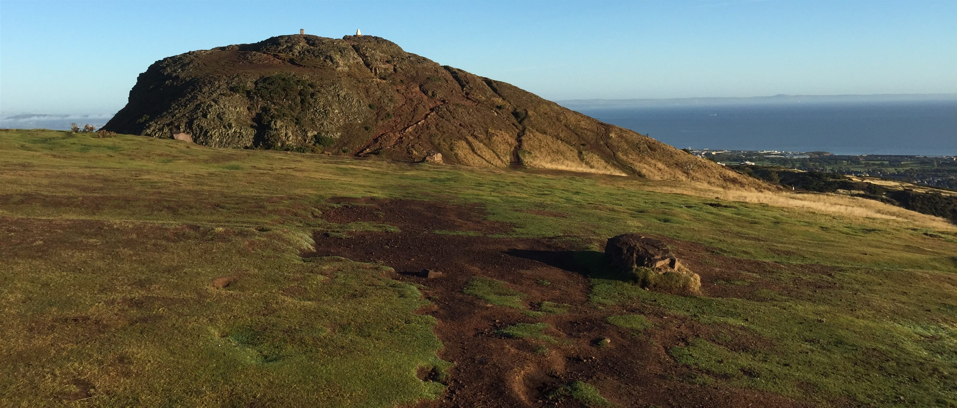 Hilltop of Arthur's Seat, with a view of the ocean in the distance. Scotland.